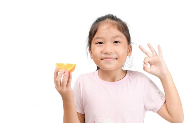 Mały śliczny Azjatykci Dziewczyna Uśmiech I Mienie Pokrojona Pomarańcze Premium Zdjęcia