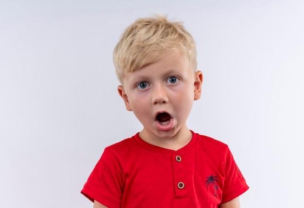 Mały śliczny Blond Chłopiec W Czerwonej Koszulce Zaskakuje Patrząc Na Białą ścianę Darmowe Zdjęcia