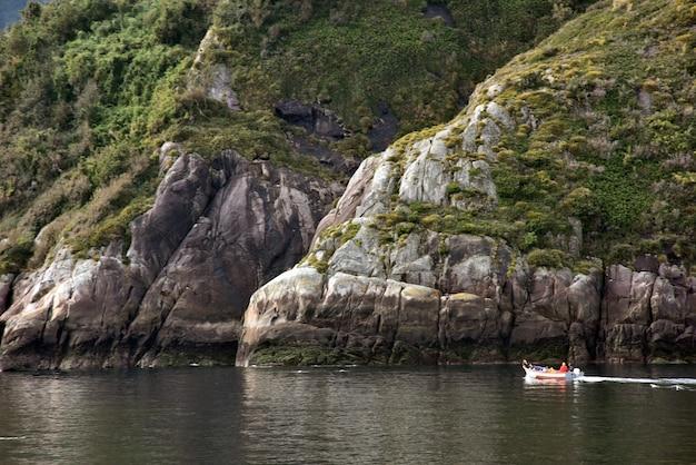 Mały Statek Na Jeziorze Otoczonym Zielonymi Trawiastymi Górami Darmowe Zdjęcia