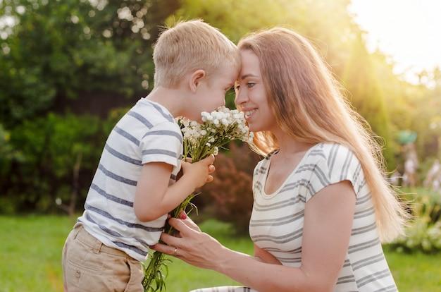 Mały Syn Daje Matce Bukiet Delikatnych Kwiatów. Premium Zdjęcia