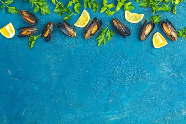 Małże, Cytryna, Natka Pietruszki Na Ciemnoniebieskiej Powierzchni Betonu Premium Zdjęcia