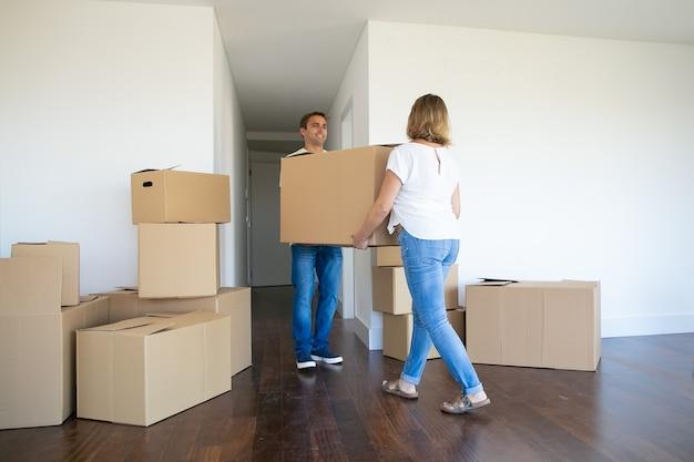 Małżeństwo Opuszcza Mieszkanie, Niosąc Kartonowe Pudełko Do Wejścia Razem Darmowe Zdjęcia