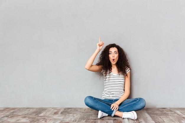 Mam Pomysł! śliczna Kobieta Siedzi Z Nogami Krzyżować Na Podłoga W Przypadkowych Ubraniach Gestykuluje Palec Wskazującego W Górę Znaczenia Eureka Nad Szarości ścianą Darmowe Zdjęcia