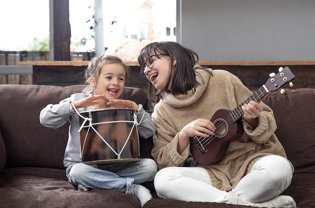 Mama Bawi Się Z Córką W Domu. Lekcje Na Instrumencie Muzycznym. Rozwój Dzieci I Wartości Rodzinne. Pojęcie Przyjaźni I Rodziny Dzieci. Darmowe Zdjęcia