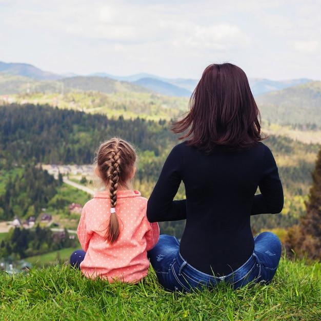 Mama i córeczka medytują na szczycie mountai Premium Zdjęcia