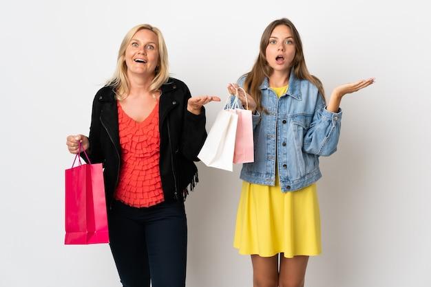 Mama I Córka Kupują Ubrania Na Białym Tle Na Białej ścianie Z Zaskoczeniem I Zszokowanym Wyrazem Twarzy Premium Zdjęcia