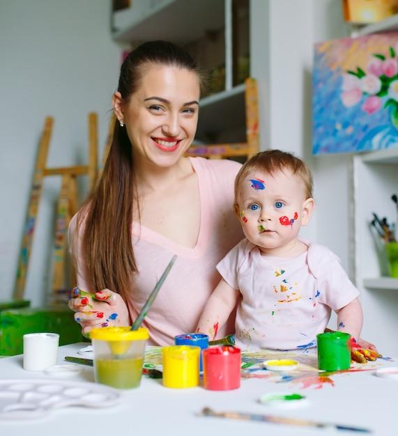 Mama i córka malują na płótnie w szkole rysunku. Premium Zdjęcia