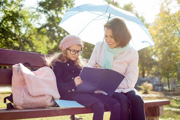 Mama I Córka Odpoczywają Razem Na ławce W Parku Miejskim Premium Zdjęcia