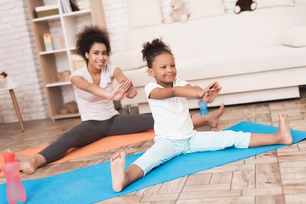 Mama i córka robią jogę w domu. Premium Zdjęcia