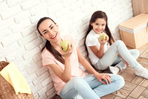 Mama i córka siedzą na podłodze z jabłkiem. Premium Zdjęcia