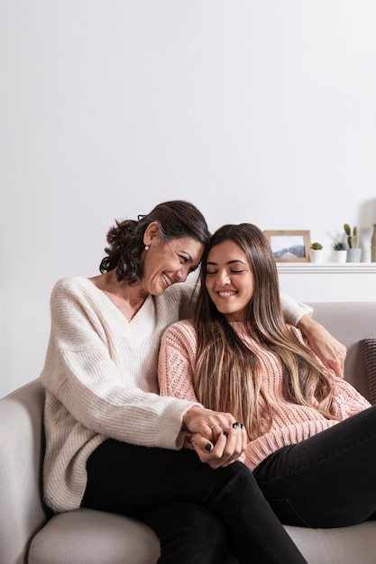 Mama I Dziewczyna Na Kanapie, Trzymając Się Za Ręce Premium Zdjęcia