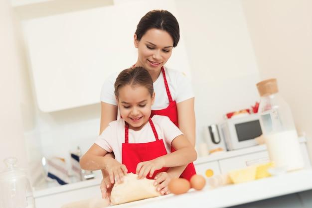 Mama i dziewczyna przygotowują ciasto w czerwonych fartuchach. Premium Zdjęcia