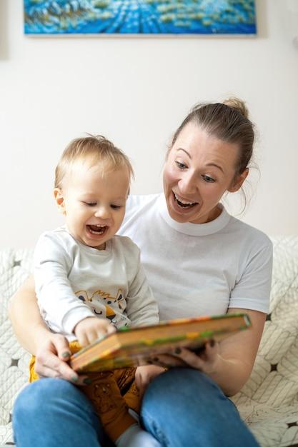 Mama I Jej Dziecko Czytają Książkę W Domu Na Sofie. Szczęśliwy I Uśmiechnięty Darmowe Zdjęcia