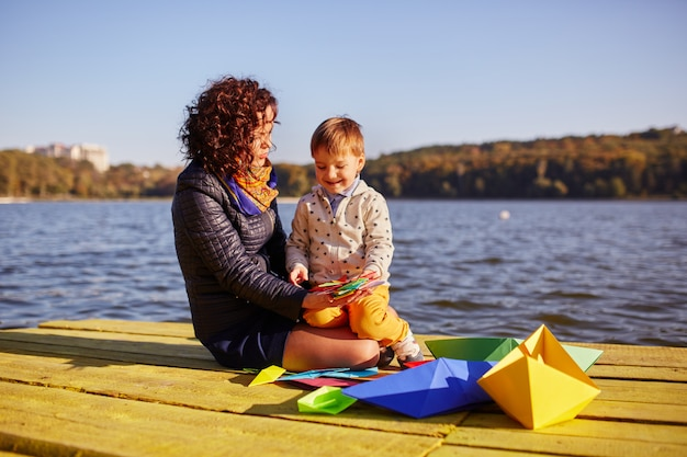 Mama I Syn Bawić Się Z Papierowymi łodziami Nad Jeziorem Darmowe Zdjęcia