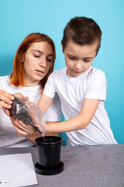 Mama I Syn Włożyli Ziemię Do Czarnej Doniczki, Aby Zasadzić Nasiona I Wyhodować Roślinę Doniczkową Na Stole Na Niebieskiej Powierzchni. Premium Zdjęcia