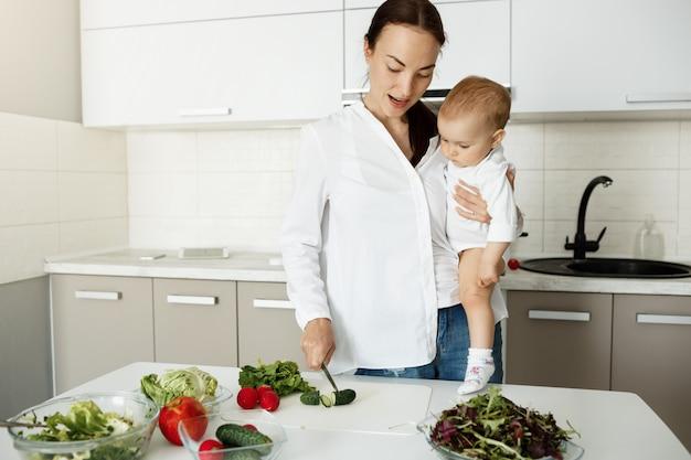Mama Nosi Dziecko I Przygotowuje Zdrowe Jedzenie, Sieka Warzywa Darmowe Zdjęcia