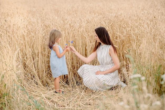 Mama Podaje Córce Kwiat Bławatka Na Polu Pszenicy Na Białorusi Premium Zdjęcia
