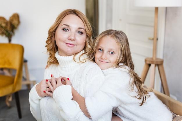 Mama Przytula Córeczkę Siedzącą Na Lekkiej Kanapie Sukienki Premium Zdjęcia