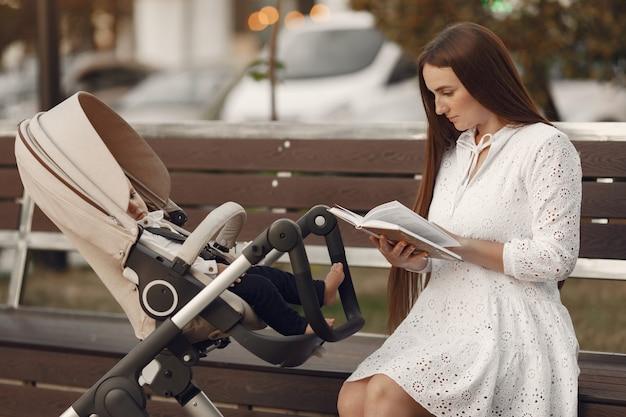 Mama Siedzi Na ławce. Kobieta Pchająca Swojego Malucha Siedzącego W Wózku. Koncepcja Rodziny. Darmowe Zdjęcia