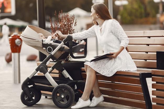 Mama Siedzi Na ławce. Kobieta Pchająca Swojego Malucha Siedzącego W Wózku. Pani Z Tabletem. Darmowe Zdjęcia