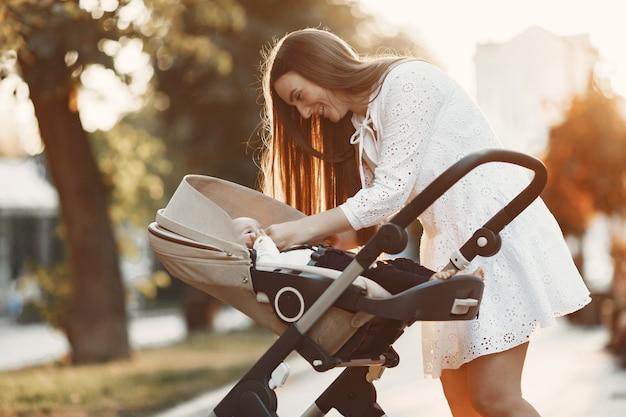 Mama Spacerująca Po Ulicy Miasta. Kobieta Pchająca Swojego Malucha Siedzącego W Wózku. Koncepcja Rodziny. Darmowe Zdjęcia