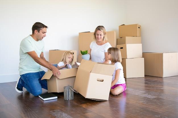 Mama, Tata I Córeczki Rozpakowują Rzeczy W Nowym Mieszkaniu, Siadają Na Podłodze I Wyjmują Przedmioty Z Otwartych Pudeł Darmowe Zdjęcia