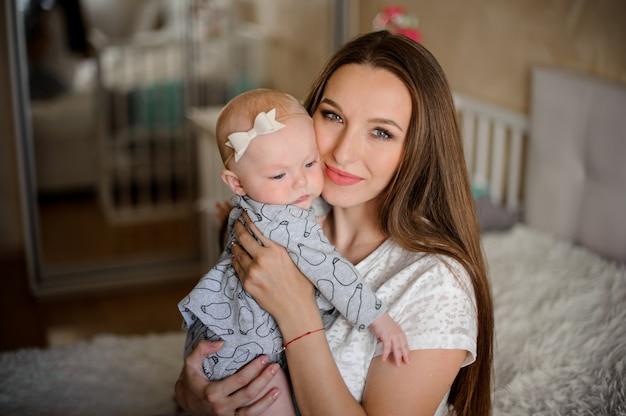 Mama Trzyma Jej Małej Córki Na Rękach Przy Pokojem Premium Zdjęcia