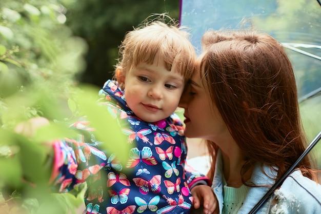 Mama Trzyma Jej Małej Córki Na Rękach Stoi Pod Parasolem W Parku Darmowe Zdjęcia