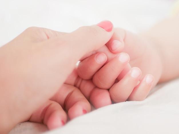 Mama Trzyma Rękę Noworodka. Zbliżenie. Miejsce Do Pisania. Umieszczanie Tekstu Rozogniskowanie. Dziecka Ręka Trzyma Palec Mama. Premium Zdjęcia