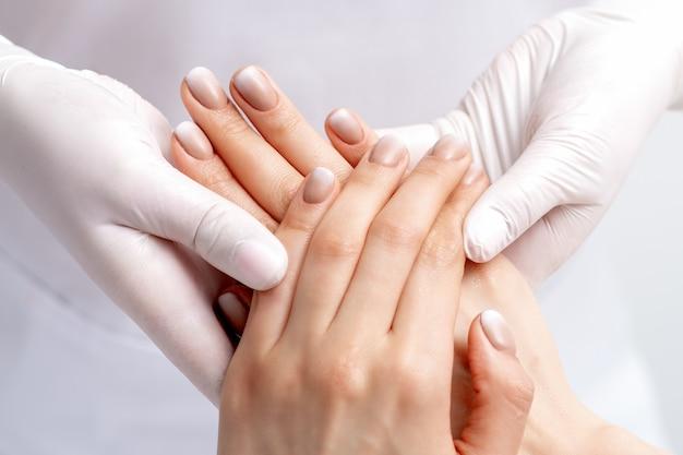 Manikiurzystka W Rękawiczkach Robi Masaż Woskiem Na Rękach Kobiet Z Manicure W Salonie Paznokci Premium Zdjęcia