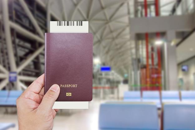 Mans Ręka Trzymająca Międzynarodowy Paszport, Czekając Przy Kasie Na Odprawę Premium Zdjęcia