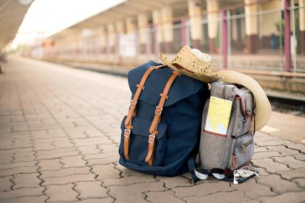 Mapa znajduje się w zabytkowej torbie z czapkami, okularami przeciwsłonecznymi, telefonami komórkowymi i słuchawkami na stacji kolejowej Premium Zdjęcia