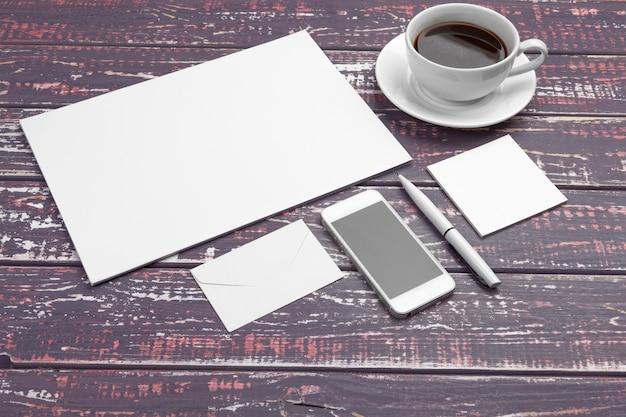 Markowanie papeterii na fioletowym biurku. widok z góry papieru, wizytówki, podkładki, długopisy i kawy. Premium Zdjęcia