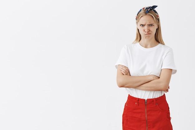 Marszczy Brwi Młoda Blond Dziewczyna Pozuje Pod Białą ścianą Darmowe Zdjęcia