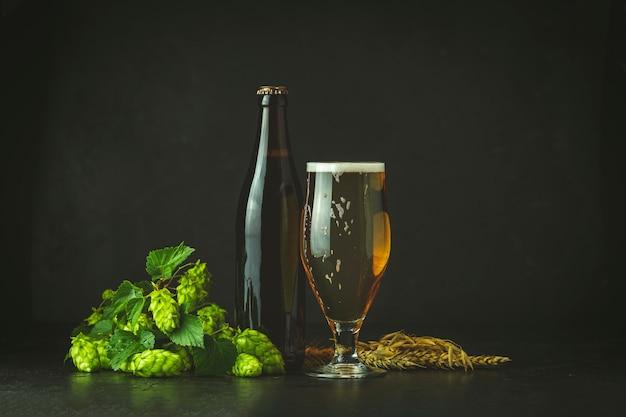 Martwa Natura Z Piwem I Chmielem W Stylu Retro. Szklanka Zimnej Spienionej Piwa Brązowej Butelki Piwa I Chmielu Na Ciemnym Tle Premium Zdjęcia