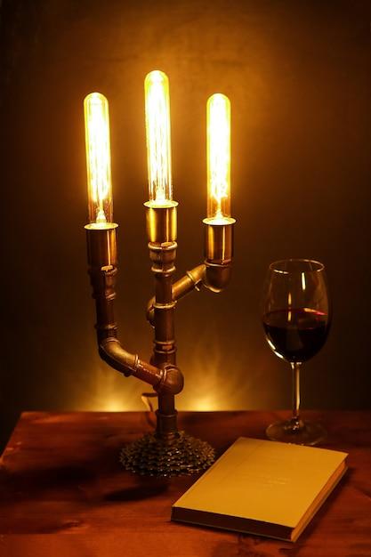 Martwa natura z ręcznie robioną lampą elektryczną, książką i lampką wina Premium Zdjęcia