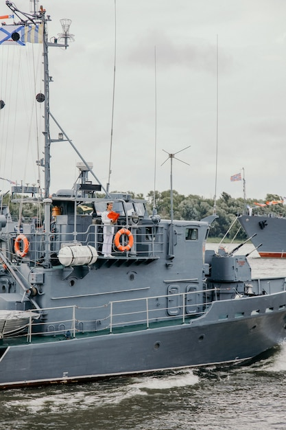 Marynarz Pozostający Na Pokładzie Okrętu Wojennego. Rosyjskie Okręty Wojenne Na Rzece Wołdze W Astrachaniu Latem W Pochmurny Dzień. Rosyjskie Okręty Wojskowe. Premium Zdjęcia