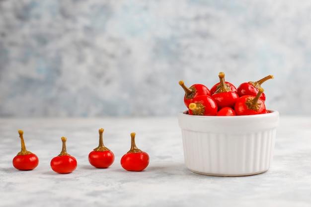 Marynowane Małe Okrągłe Czerwone Gorące Wiśniowe Papryczki Chili Na Szarym Betonie Darmowe Zdjęcia