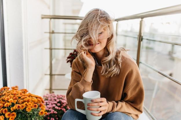 Marzycielska Blondynka Siedzi Na Balkonie Z Filiżanką Herbaty. Oszałamiająca Modelka Na Tarasie. Darmowe Zdjęcia