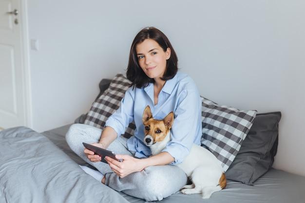 Marzycielska brunetka modelka w piżamie siedzi ze skrzyżowanymi nogami na wygodnym łóżku w sypialni, trzyma nowoczesny tablet, obejmuje swojego zwierzaka Premium Zdjęcia
