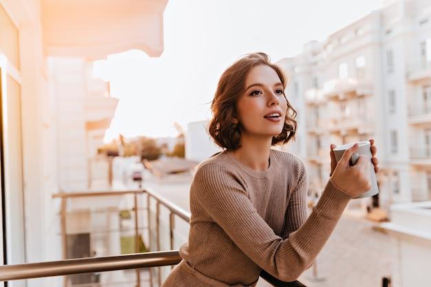Marzycielska Ciemnooka Dziewczyna Pije Herbatę Na Balkonie. Zdjęcie Kaukaski Dobrze Ubrana Modelka Trzyma Filiżankę Kawy. Darmowe Zdjęcia