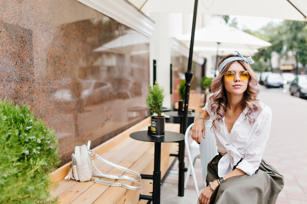 Marzycielska Dziewczyna W Białej Koszuli Z Małym Plecakiem Czeka Na Chłopaka W Kawiarni Na świeżym Powietrzu Darmowe Zdjęcia