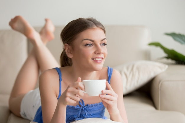 Marzycielska Kobieta Relaksuje Na Wygodnej Kanapie, Cieszy Się Filiżankę Coffe Darmowe Zdjęcia