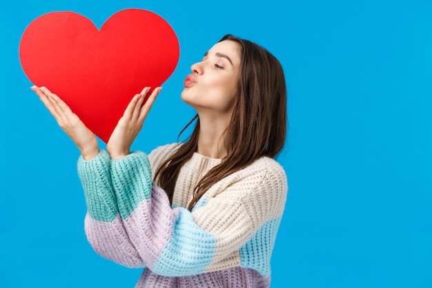 Marzycielska Młoda Kobieta Pielęgnuje Swój Związek, Przygotowuje Prezent Na Walentynki, Całuje Wielkie Słodkie Czerwone Serce Na Lewej Stronie, Stoi Niebiesko Zachwycona I Optymistyczna Premium Zdjęcia