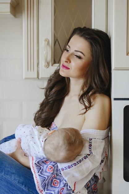 Marzycielska piękna mama siedzi z dzieckiem na rękach Darmowe Zdjęcia