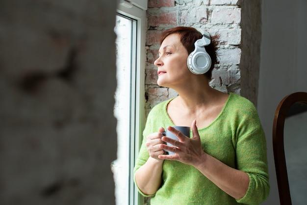 Marzycielska starsza kobieta słucha muzykę Darmowe Zdjęcia