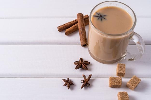 Masala chai herbata w kubku, brązowy cukier, laski cynamonu i anyżu na białym stole. Premium Zdjęcia