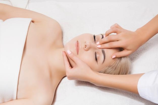 Masaż twarzy. zbliżenie: młoda kobieta odbiera masaż spa w salonie piękności i spa przez kosmetyczki. spa pielęgnacja skóry i ciała. pielęgnacja twarzy piękna. kosmetyka. Premium Zdjęcia