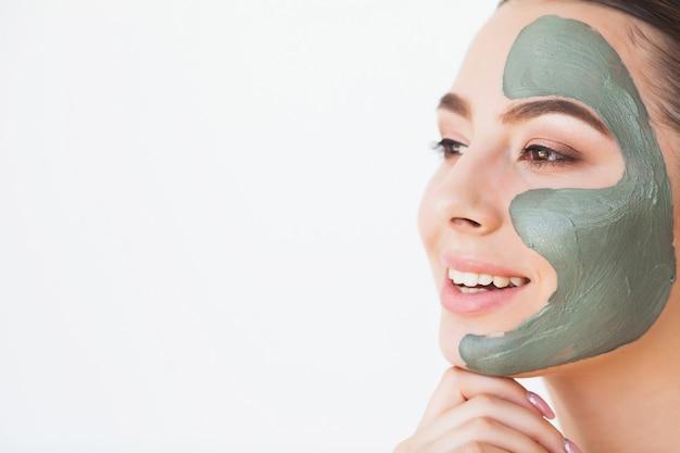 Maska. piękna uśmiechnięta kobieta stosuje maskę na twarzy Premium Zdjęcia