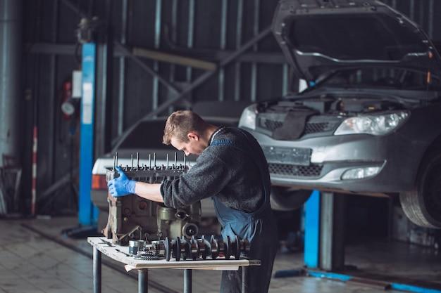 Master Zbiera Przebudowany Silnik Do Samochodu. Premium Zdjęcia